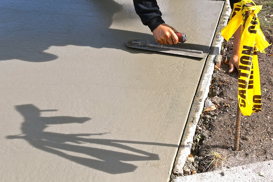 Concrete contractor smoothing a concrete driveway